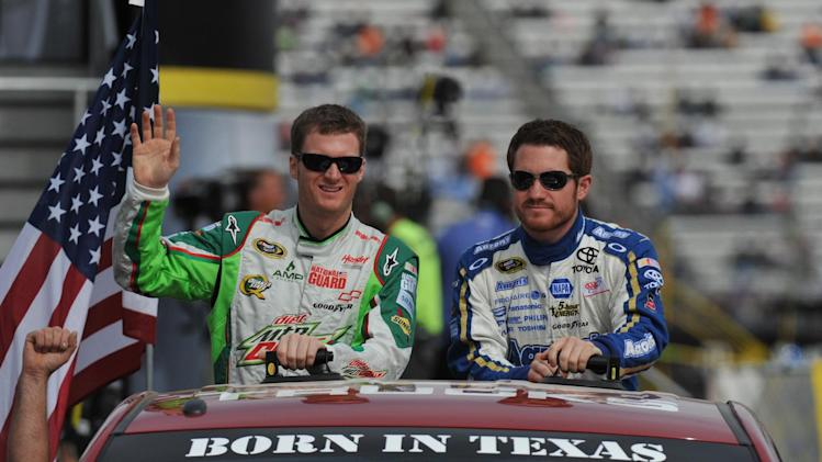 Dale Earnhardt Jr., left, acknowledges fans as he rides with Brian Vickers during driver introductions before the NASCAR Sprint Cup Series auto race at Martinsville Speedway, Sunday, Oct. 28, 2012, in Martinsville, Va. (AP Photo/Don Petersen)