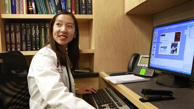 In this Tuesday, Aug. 14, 2012 photo Leana Wen, of Boston, who is doing her medical residency in emergency medicine at Harvard-affiliated Brigham and Women's Hospital and Massachusetts General Hospital, works on a computer at Brigham and Women's in Boston. Wen chose emergency medicine because the hours are more flexible than those of primary care physicians. (AP Photo/Steven Senne)
