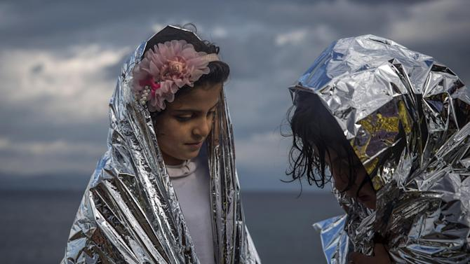 Two girls wear thermal blankets provided by volunteers after their arrival from the Turkish coast to the northeastern Greek island of Lesbos, on Wednesday, Nov. 25, 2015. About 5,000 migrants reaching Europe each day over the so-called Balkan migrant route. The refugee crisis is stoking tensions among the countries on the so-called Balkan migrant corridor — Greece, Macedonia, Serbia, Croatia and Slovenia. (AP Photo/Santi Palacios)