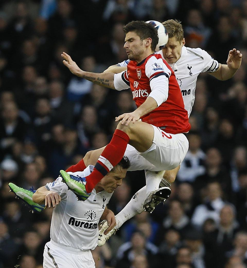 Tottenham Hotspur's Michael Dawson, rear right, heads the ball with Arsenal's Olivier Giroud, as they jump above Tottenham's Scott Parker during the English Premier League soccer match between Tottenham and Arsenal at Tottenham's White Hart Lane stadium in London, Sunday, March 3, 2013. (AP Photo/Kirsty Wigglesworth)