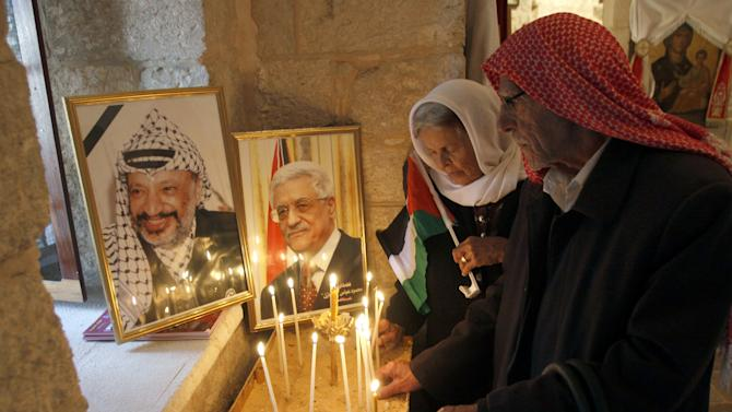 Palestinian Christians light candles next to portraits of former Palestinian leader Yasser Arafat, left, and President Mahmoud Abbas, right, at St. George Melkite Greek Catholic Church, also know as the Church of the Ten Lepers, in the West Bank village of Burqin near the town of Jenin,  Friday, Nov. 30, 2012. Palestinians celebrated the U.N. General Assembly votes on a resolution to upgrade the status of the Palestinian Authority to a nonmember observer state. (AP Photo/Mohammed Ballas)