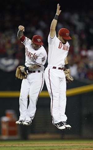 Arizona Diamondbacks Ryan Roberts, left, and Gerardo Parra celebrate their team's 8-1 victory over the Milwaukee Brewers in Game 3 of baseball's National League division series Tuesday, Oct. 4, 2011, in Phoenix.  (AP Photo/Matt York)