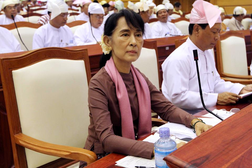 FILE - In this Tuesday, Aug. 14, 2012 file photo, Myanmar's opposition leader Aung San Suu Kyi, center, attends a regular session of the parliament at Myanmar Lower House in Naypyitaw, Myanmar. (AP Photo/Khin Maung Win)