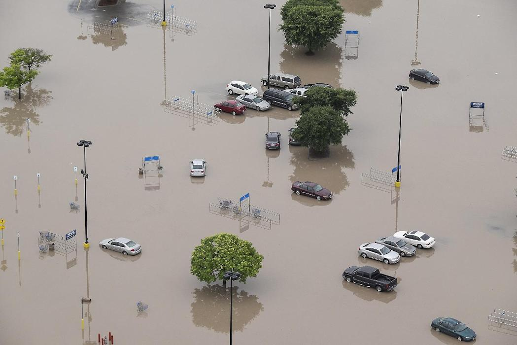 In this aerial photo a parking lot of Wal-Mart is submerged after the San Marcos River flooded in San Marcos, Texas, Sunday, May 24, 2015. Record...