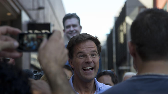 A poster of left-wing Socialist Party leader Emile Roemer, rear, is seen as Dutch Prime Minister and Liberal Party leader Mark Rutte, center, campaigns four days ahead of the national elections, in Dordrecht, south-western Netherlands, Saturday, Sept. 8, 2012.  With the debt crisis plunging the European Union into the darkest days of its history,  many commentators are wondering whether Wednesday's Dutch elections will radically transform their relationship with the EU,  one of the nations that forged unity from the ashes of World War II. (AP Photo/Peter Dejong)