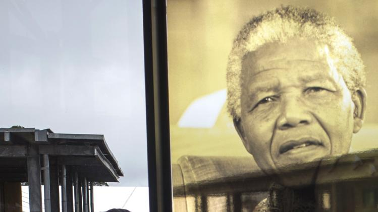 A soldier walks past an image of Nelson Mandela on the grounds of the Nelson Mandela Museum in Qunu
