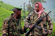 "Two M23 rebels patrol in rebel-held territory on Kavumu hill in North Kivu, eastern Democratic Republic of the Congo (DRC), earlier this month. UN sanctions experts have ""overwhelming evidence"" that Rwanda has breached an arms embargo to aid rebels in the Democratic Republic of Congo, according to a report obtained by AFP"