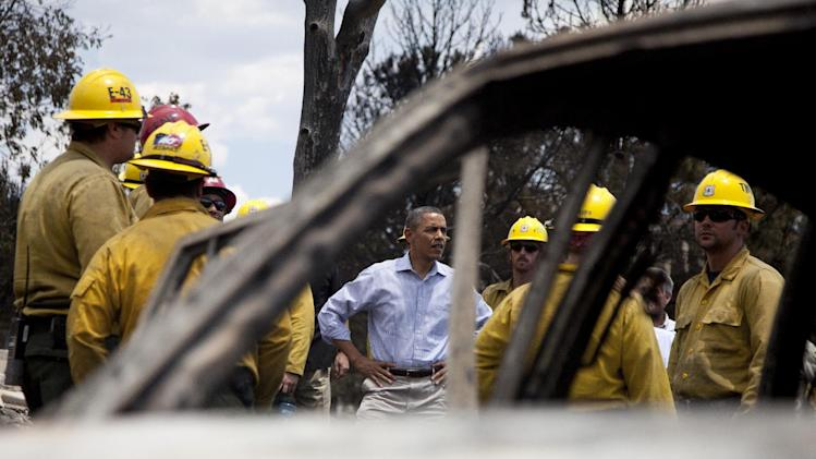 President Barack Obama is seen through a burned out car as he talks with firefighters as he tours the Mountain Shadow neighborhood devastated by wildfires, Friday, June 29, 2012, in Colorado Springs, Colo. (AP Photo/Carolyn Kaster)