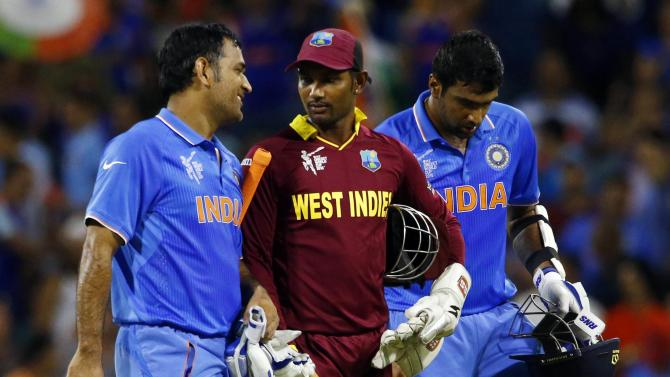 India's batsmen Ravichandran Ashwin and MS Dhoni walk with West Indies' wicket keeper Denesh Ramdin off the field together following India's four wicket victory at the Cricket World Cup in Perth