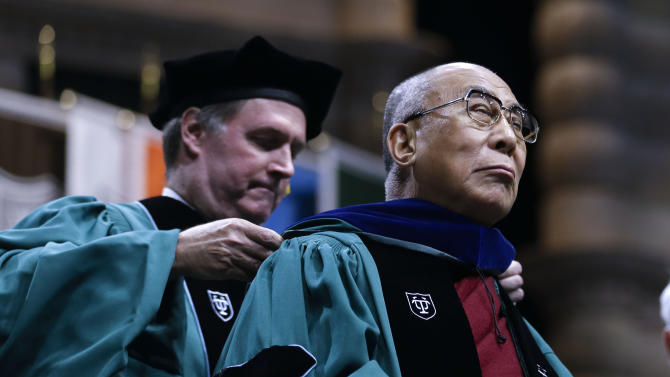 The Dalai Lama receives an honorary degree at Tulane University's 179th commencement ceremony at the Mercedes-Benz Superdome in New Orleans on Saturday, May 18, 2013. He also delivered the commencement address. (AP Photo/Gerald Herbert)