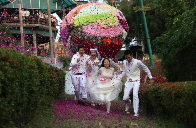 Thai grooms and their brides run during a wedding ceremony ahead of Valentine's Day in Prachin Buri province