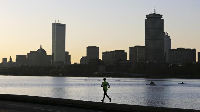 A solitary runner heads down the banks of the Charles River in Cambridge, Mass., in front of the Boston skyline, at dawn the morning after explosions killed three and injured more than 140 at the Boston Marathon, Tuesday, April 16, 2013. The bombs that blew up seconds apart at the finish line of one of the world's most storied races left the streets spattered with blood and glass, and gaping questions of who chose to attack at the Boston Marathon and why. (AP Photo/Charles Krupa)