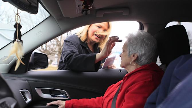 The Rev. Patricia Anderson Cook gives the blessing to Suzanne Reichart as she sits inside her car during drive thru Ash Wednesday services at Mt. Healthy United Methodist Church, Wednesday, Feb. 22, 2012, in Mt. Healthy, Ohio. (AP Photo/Al Behrman)