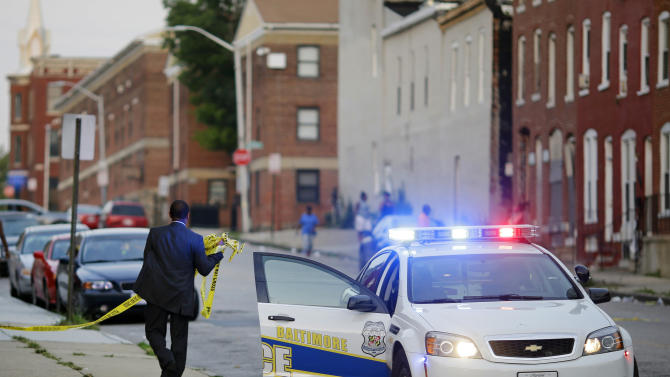 In this July 30, 2015 picture, a member of the Baltimore Police Department removes crime scene tape from a corner where a victim of a shooting was discovered in Baltimore. Murders are spiking again in Baltimore, three months after Freddie Gray's death in police custody sparked riots. This year's monthly bloodshed has twice reached levels unseen in a quarter-century. In May, Baltimore set a 25-year high of 42 recorded killings. After a brief dip in June, the homicide is soaring again. (AP Photo/Patrick Semansky)