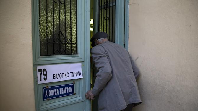 Man enters a polling station to cast his ballot during a referendum vote in Athens, Greece