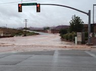 This photo released by the St. George Police Department shows a flooded street after a dike broke and sent floodwaters through the town of Santa Clara, Utah, Tuesday, Sept. 11, 2012. Officials in Santa Clara say they're inspecting whether people can return to about 60 homes and 15 businesses that were evacuated after a dike broke and sent floodwaters through town. City Parks and Recreation Director Brad Hays said a retention pond fed by the Tuacahn Wash filled up after heavy rains Tuesday morning. Authorities ordered homes and businesses below the pond to evacuate about noon, and the dike broke about 45 minutes later. No injuries have been reported from the flooding. (AP Photo/St. George Police Department)