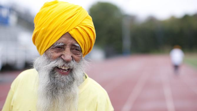 Centenarian Fauja Singh smiles on the track in Toronto, Thursday, Oct. 13, 2011. One-hundred-year-old Singh, originally from India now living in London,  England, is competing in Toronto's Waterfront Marathon on Sunday.  (AP Photo/The Canadian Press, Chris Young)