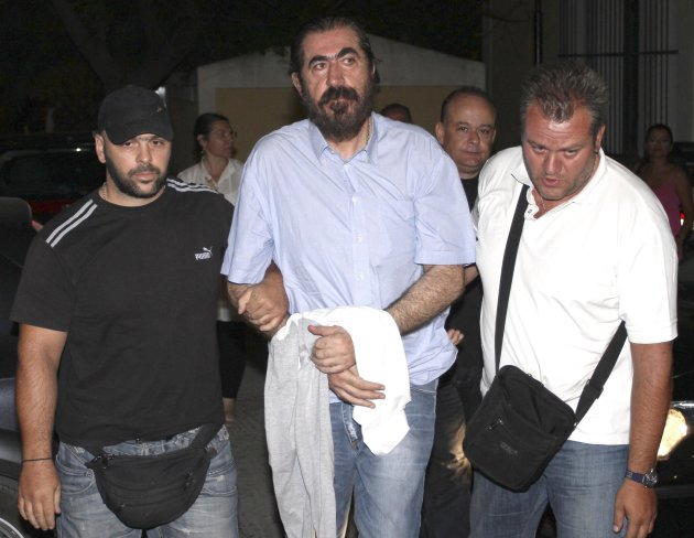 Makis Psomiadis, center, the former chairman of Greek club Kavala, is escorted by plain clothed police officers, arrives at a court in Athens, on Thursday, Sept. 15, 2011. Psomiadis has been arrested