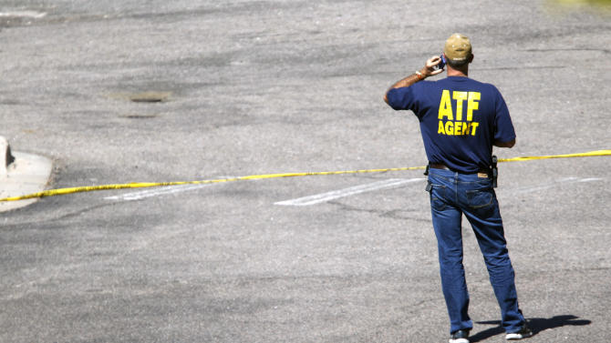 """An agent from the Bureau of Alcohol Tobacco and Firearms makes a call outside the Century 16 theatre east of the Aurora Mall in Aurora, Colo., on Friday, July 20, 2012. Authorities report that 12 died and more than three dozen people were shot during an assault at the theatre during a midnight premiere of """"The Dark Knight."""" (AP Photo/David Zalubowski)"""