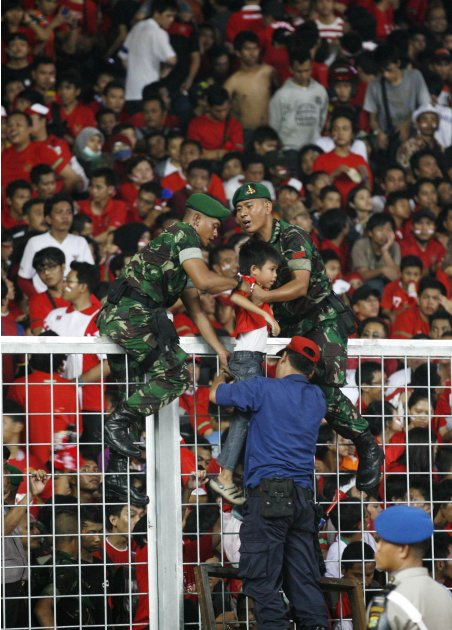 Indonesian soldiers pull out a child from the crowd during the SEA Games soccer final between Malaysia and Indonesia at the Gelora Bung Karno stadium in Jakarta