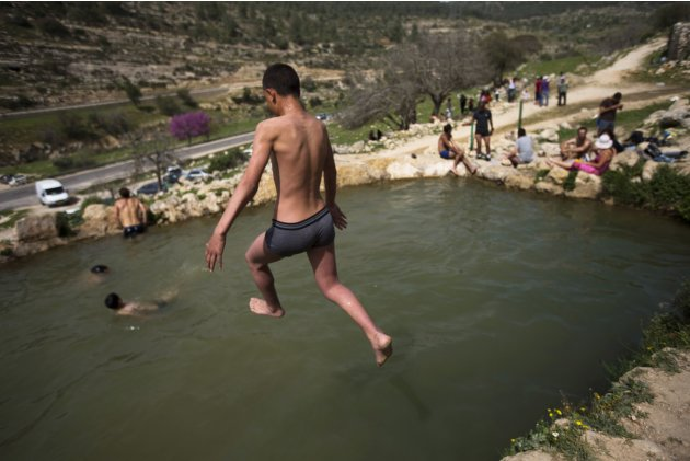 Youths cool off at a spring near the outskirts of Jerusalem