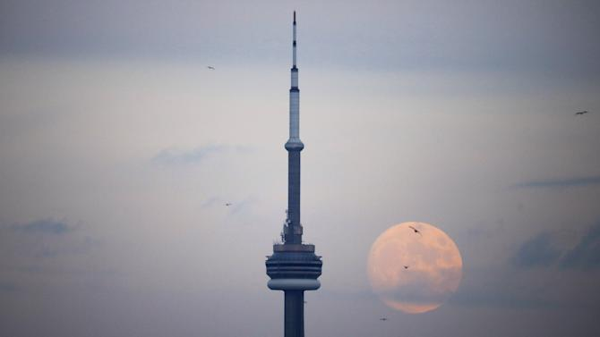 The moon rises behind the CN Tower, a Canadian landmark, in Toronto