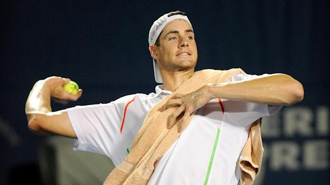 John Isner throws the balls to fans in the stands after winning his match against Bradley Klahn, during the Winston-Salem Open, at Wake Forest University in Winston Salem, North Carolina, on August 19, 2014