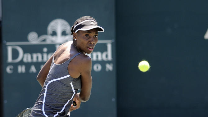 Venus Williams prepares to hit a backhand shot against her sister Serena Williams during the semifinals at the Family Circle Cup tennis tournament in Charleston, S.C., Saturday, April 6, 2013. Serena won 6-1, 6-2. (AP Photo/Stephen Morton)