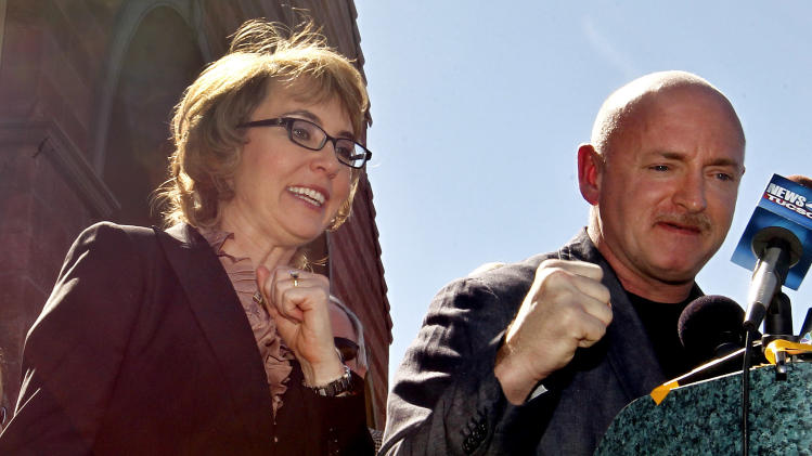 "Former Rep. Gabrielle Giffords, left, shouts ""fight, fight, fight"" as she and husband,  Mark Kelly,  pump their fists together as they returned to the site of a shooting that left Giffords critically wounded on Wednesday, March 6, 2013, in Tucson, Ariz.  Giffords urged senators to pass background checks for gun purchases.  (AP Photo/Ross D. Franklin)"