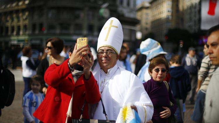 A soccer fan dressed up as Pope Francis holds Argentina's national flag while taking a selfie with a woman, before the team's World Cup final soccer match against Germany, in Buenos Aires