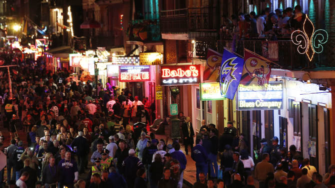 People walk along Bourbon Street in downtown New Orleans, as revelers gathered in the city's French Quarter, Friday, Feb. 1, 2013. The city kicked off NFL football Super Bowl weekend as it awaits for Sunday's game between the San Francisco 49ers and the Baltimore Ravens at the Superdome. (AP Photo/Julio Cortez)