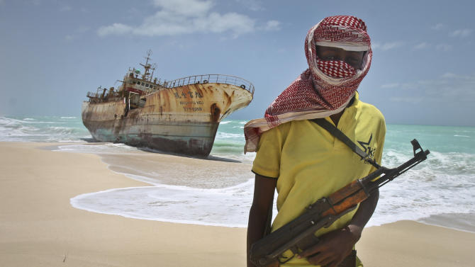 "FILE - In this Sunday, Sept. 23, 2012 file photo, masked Somali pirate Hassan stands near a Taiwanese fishing vessel that washed up on shore after the pirates were paid a ransom and released the crew, in the once-bustling pirate den of Hobyo, Somalia. Frustrated by a string of failed hijacking attempts, Somali pirates have turned to a new business model: transporting weapons and providing ""security"" for ships illegally plundering Somalia's fish stocks - the same scourge that launched the Horn of Africa's piracy era eight years ago. (AP Photo/Farah Abdi Warsameh, File)"