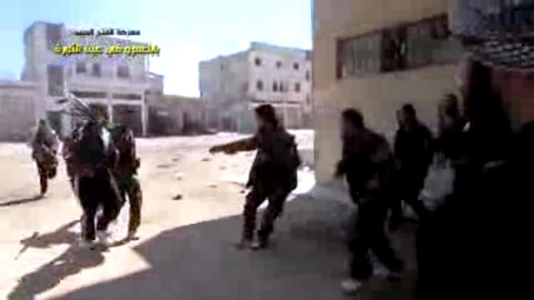 In this image taken from video obtained from the Shaam News Network, which has been authenticated based on its contents and other AP reporting, Syrian rebels capture a member of Syrian regime forces in Homs, Syria, Tuesday, March 26, 2013. Mortars rounds struck several areas of Damascus on Tuesday, killing several people, a government official said, while anti-regime activists said Syrian troops seized control of a neighborhood in the central city of Homs that is considered a symbol of opposition to President Bashar Assad's regime. (AP Photo/Shaam News Network via AP video)