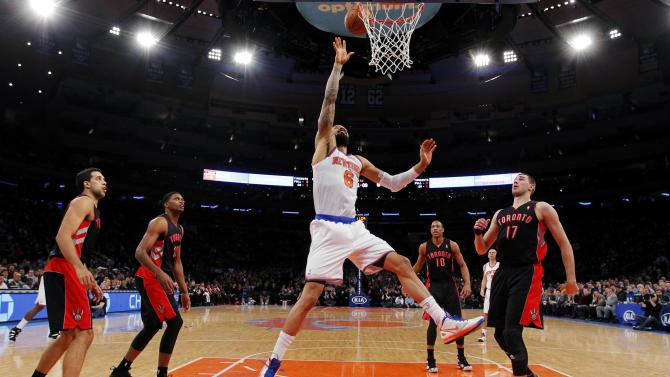 New York Knicks' Chandler shoots for a basket beteen Toronto Raptors players during  their NBA basketball game in New York