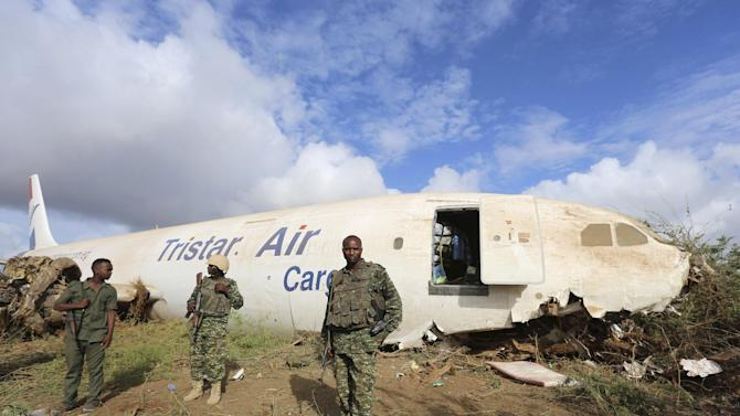 Ugandan soldiers serving in AMISOM and a Somalia soldier stand guard as they secure the site where a Tristar Air Airbus A300-200F cargo plane crash-landed in Arbiska outside Somalia's capital Mogadishu