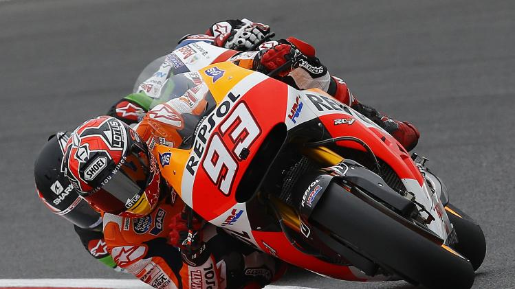 Honda MotoGP rider Marc Marquez of Spain competes with Honda MotoGP rider Scott Redding of Britain during the qualifying session for the British Grand Prix at the Silverstone Race Circuit