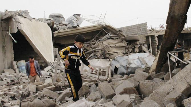 A boy walks in rubble at the scene of a car bomb attack in al-Mouafaqiyah, a village inhabited by families from the Shabak ethnic group, near the city of Mosul, 225 miles (360 kilometers) northwest of Baghdad, Iraq, Monday, Dec. 17, 2012. Three car bomb explosions in Iraq's north on Monday, killing and wounding scores of people, police said. (AP Photo)