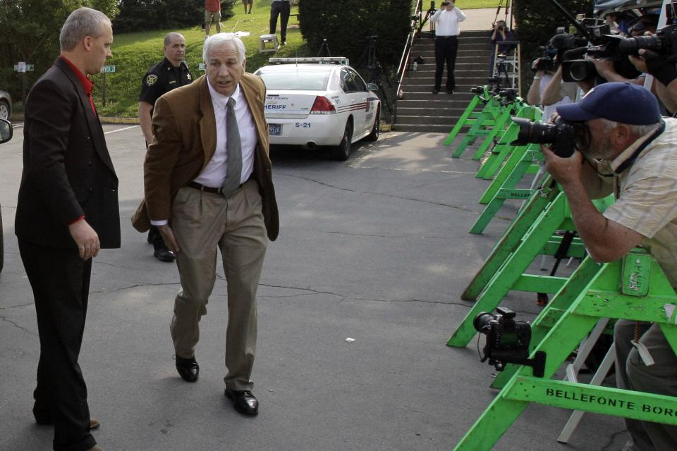 Former Penn State University assistant football coach Jerry Sandusky, third from left, arrives at the Centre County Courthouse in Bellefonte, Pa., Friday, June 22, 2012. Sandusky is accused of sexual abuse of 10 boys over a 15-year period.  (AP Photo/Gene J. Puskar)