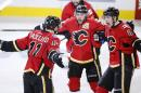 Calgary Flames' Mikael Backlund, left, from Sweden, celebrates his goal against the Anaheim Ducks with Kris Russell, middle, and Joe Colborne during overtime of Game 3 in the second round of the NHL Stanley Cup hockey playoffs, Tuesday, May 5, 2015, in Calgary, Alberta. (AP Photo/The Canadian Press, Larry MacDougal)