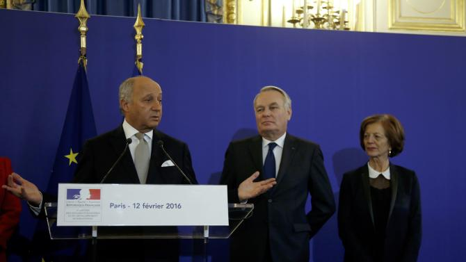 Outgoing French Foreign Minister Laurent Fabius delivers a speech next to newly-appointed Foreign Minister Jean-Marc Ayrault and his wife Brigitte during the official handover ceremony at the Quai d'Orsay in Paris