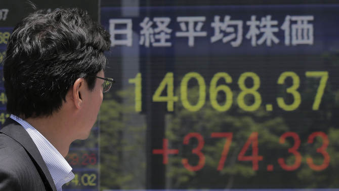 A man walks by the electronic stock board of a securities firm in Tokyo, Tuesday, May 7, 2013. Japan's benchmark stock index, reopening after a long weekend holiday, surged Tuesday in the wake of a U.S. jobs report issued late last week that handily beat expectations. (AP Photo/Itsuo Inouye)
