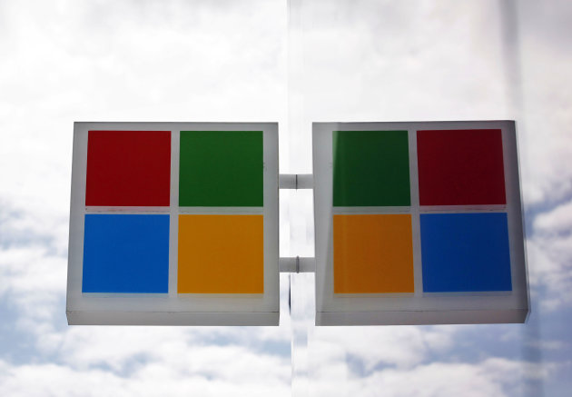 The new Microsoft logo is seen reflected in windows at a company store Thursday, Aug. 23, 2012, in Seattle. Microsoft's new corporate logo sets the stage for a wave of products designed to cast the wo
