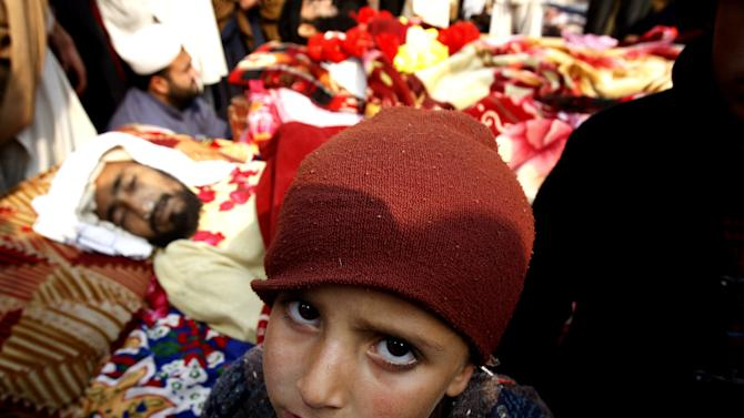 A boys sits next to his father's dead body in Peshawar, Pakistan, Wednesday, Jan. 16, 2013. Hundreds of villagers from northwest Pakistan protested Wednesday the killing of 18 of their relatives in an overnight raid that they blamed on security forces, displaying the bodies of the victims in the provincial capital. (AP Photo/Mohammad Sajjad)