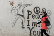 A Syrian woman walks past graffiti in the rebel-held Syrian city of Minbej. The Syrian regime rejected a UN call for a unilateral ceasefire on Wednesday as rebels confronted columns of tanks and troops sent to retake a town on the road to main battleground city Aleppo