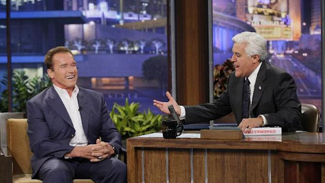 "This Oct. 8, 2012 photo released by NBC shows former California Gov. Arnold Schwarzenegger, left, is interviewed by host Jay Leno on ""The Tonight Show with Jay Leno"" in Burbank, Calif. NBC has cut the salary of the popular late night talk show host in an an effort by new owner Comcast Corp., to reboot the network.  (AP Photo/NBC, Paul Drinkwater)"