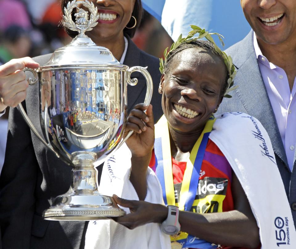 Women's winner Sharon Cherop of Kenya smiles as she holds the trophy at the finish area of the 2012 Boston Marathon in Boston, Monday, April 16, 2012. (AP Photo/Elise Amendola)