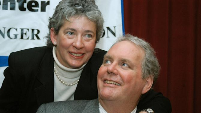 FILE - In this Feb. 10, 2004 file photo, Lucinda Marker wraps her arm around her husband John Tull after a news conference at Beth Israel Hospital in New York. Tull, a New Mexico man who nearly lost his life to bubonic plague 12 years ago has died. Lucinda Marker said John Tull, 65, died Wednesday, June 25, 2014 in a Santa Fe hospital. Marker says Tull was diagnosed a month ago with a rare cancer. She says doctors didn't believe it was related to the plague. According to doctors, the couple were infected by flees at their Santa Fe home but experienced symptoms while vacationing in New York City in November 2002. Marker recovered within days but Tull was hospitalized for more than two months. Marker says a memorial service is planned for Aug. 9. (AP Photo/Jennifer Szymaszek)