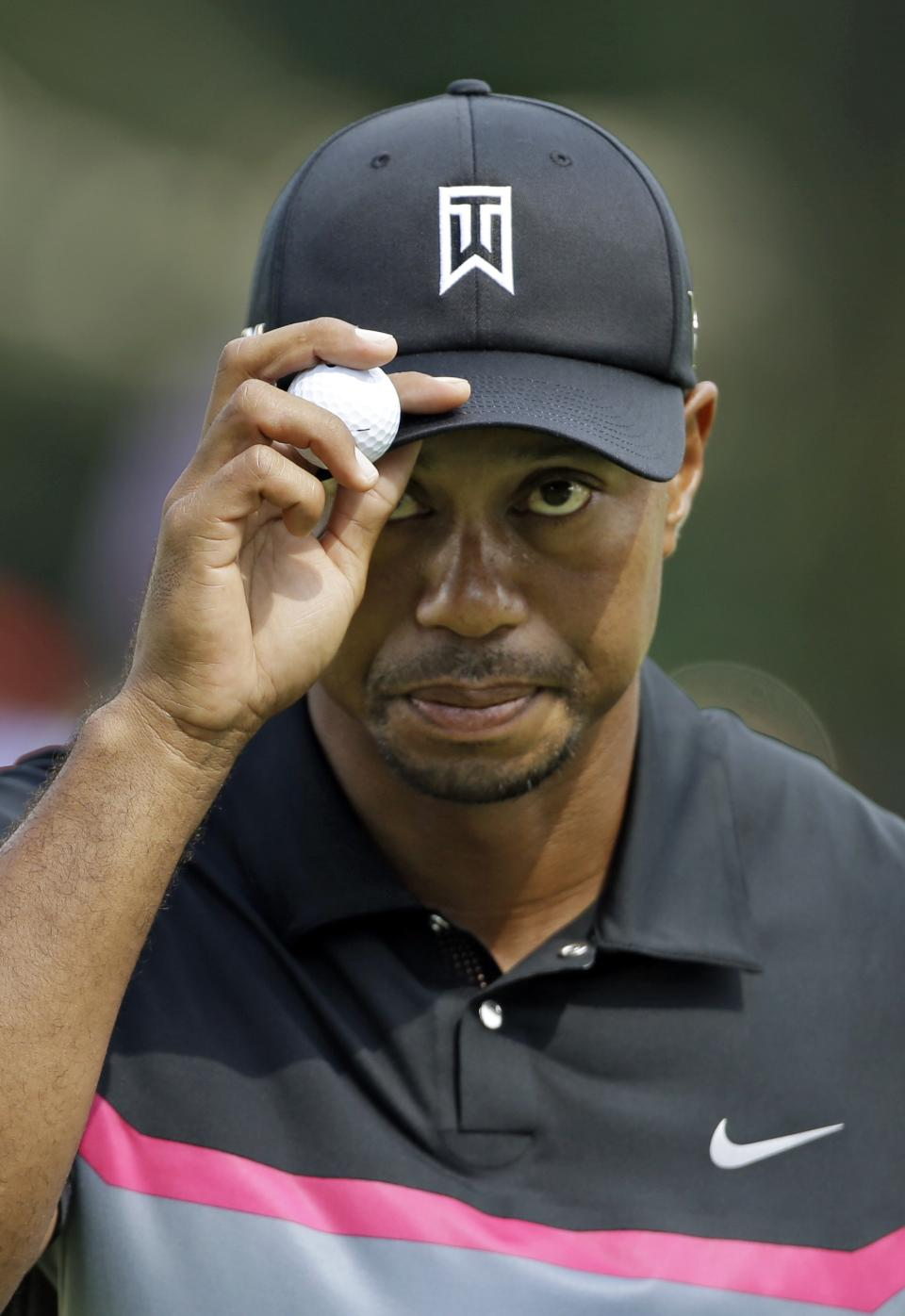 Tiger Woods acknowledges fans after saving par on the 17th hole during the first round of the Bridgestone Invitational golf tournament Thursday, Aug. 1, 2013 at Firestone Country Club in Akron, Ohio. (AP Photo/Mark Duncan)