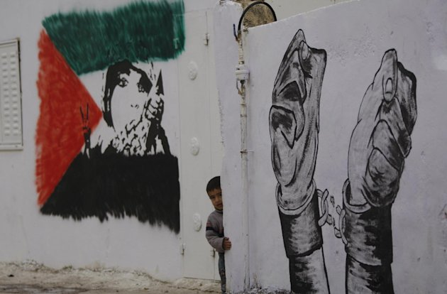 Palestinian relatives of prisoner Younis Jahjouh decorate the street ahead of his release from Israeli prisons in the Qalandia refugee camp near the West Bank city of Ramallah, Saturday, Dec 17, 2011.