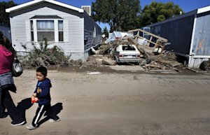 In this Sept. 24, 2013 photo, a child walks among homes …